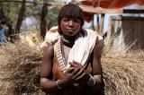 Hamar vrouw met draagt bos takken op haar rug; kapsel is mengsel van rode klei en vet. Foto: Maurice van Steen