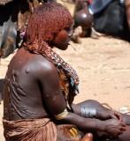 Hamar vrouw met littekens op haar rug als gevolg van het ritueel geselen. kapsel is mengsel van rode klei en vet. Foto: Maurice van Steen