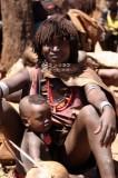 Hamar vrouw met kind kapsel is mengsel van rode klei en vet. Foto: Maurice van Steen