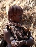 Hamar vrouw met leder kledingstuk dat voorzien is van schelpen. Foto: Maurice van Steen
